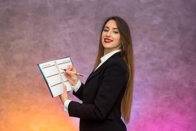Piękna biznesowa dama wskazująca długopisem w schowku proponująca podpisanie umowy