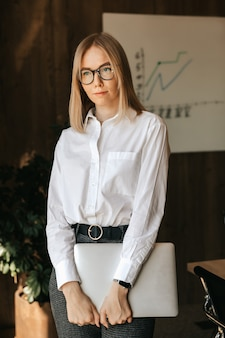 Piękna biznesowa dziewczyna w białej koszuli i okularach stoi z laptopem w dłoniach w biurze na tle tablicy z wykresem rozwoju firmy