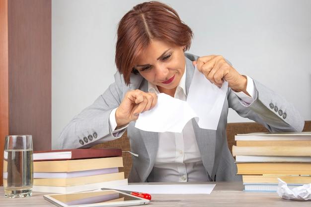 Piękna biznesowa kobieta łzawi biały papier na pół