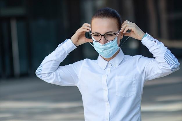 Piękna biznesowa kobieta, młoda dziewczyna stawia na medyczną ochronną maskę na jej twarzy, w białej koszula w szkłach outdoors, opieka zdrowotna przy pracą, praca, biuro. koncepcja koronawirusa, wirusa, epidemii, covid-19