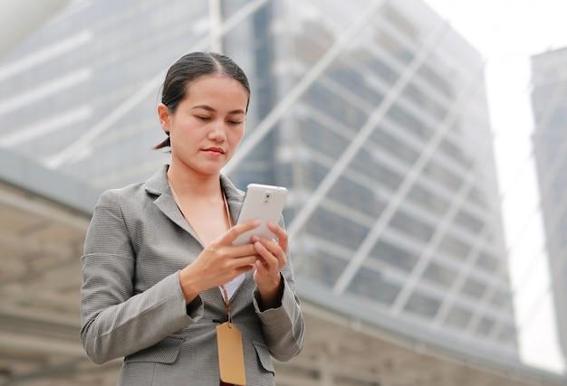 Piękna biznesowa kobieta pracuje na smartphone w jej rękach outdoors.
