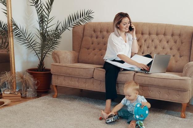 Piękna biznesowa kobieta pracuje w domu. koncepcja wielozadaniowości, niezależności i macierzyństwa