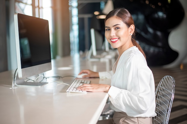 Piękna biznesowa kobieta pracuje z jej komputerem