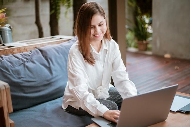 Piękna biznesowa kobieta pracuje z jej laptopem w sklep z kawą
