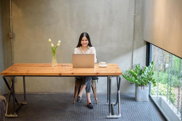 Piękna biznesowa kobieta pracuje z laptopem w sklep z kawą