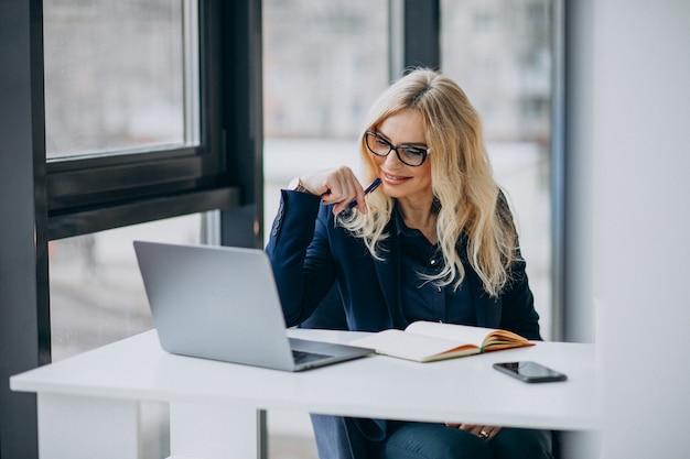 Piękna biznesowa kobieta przy biurem