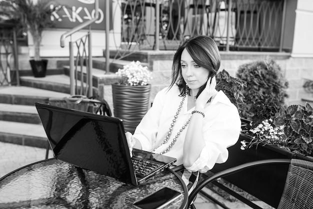 Piękna biznesowa kobieta siedzi w miejskiej kawiarni i pracuje ze swoim laptopem. obraz czarno-biały
