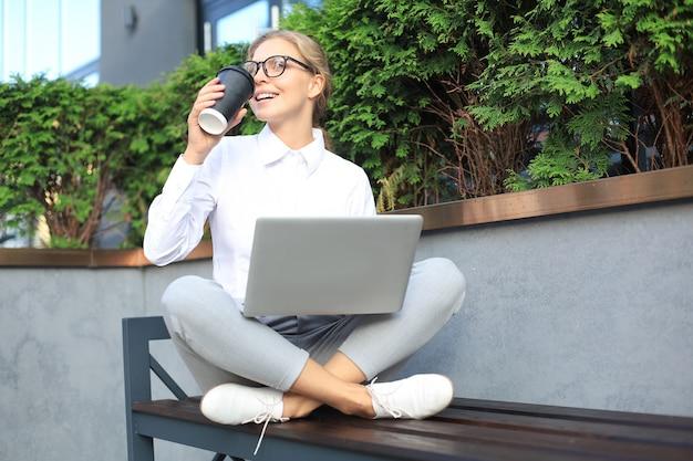 Piękna biznesowa kobieta siedzi w pobliżu centrum biznesowego i za pomocą laptopa.