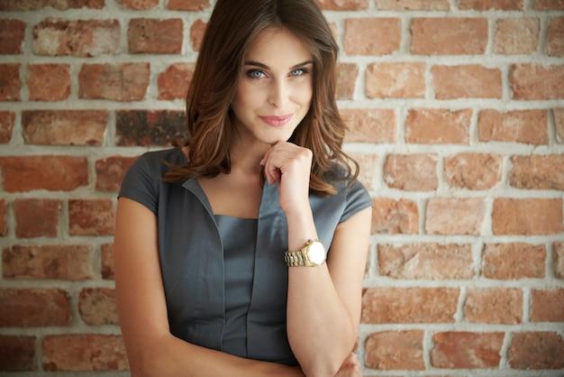 Piękna biznesowa kobieta stojąca przed ścianą