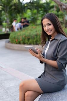 Piękna biznesowa kobieta używa ipad dla plenerowego działania