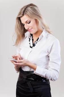 Piękna biznesowa kobieta w białej koszula z smartphone na bielu