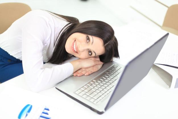 Piękna biznesowa kobieta w biurze na laptopa