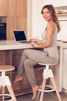 Piękna biznesowa kobieta w domowych ubraniach używa laptop.