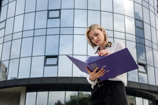 Piękna biznesowa kobieta z folderu pozuje naprzeciwko centrum biznesowego