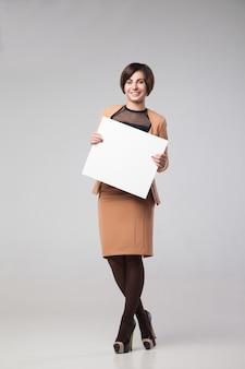 Piękna biznesowa kobieta z pustą kartą. na białym tle nad szarym tłem.