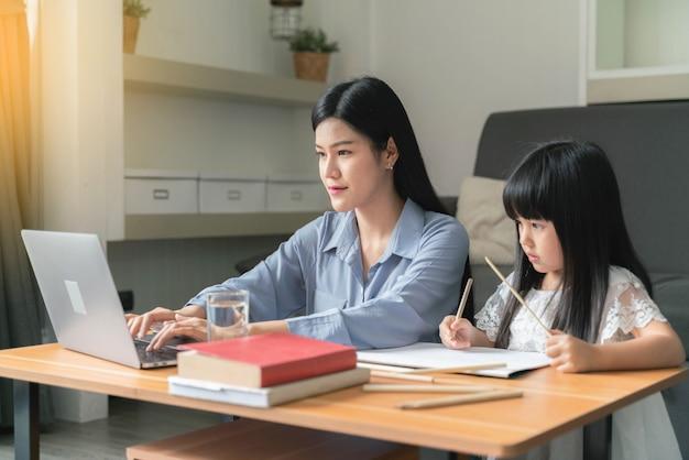 Piękna biznesowa mama używa laptopa z dziećmi w domu