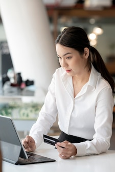Piękna bizneswoman azjatyckiego trzymając kartę kredytową i za pomocą tabletu siedząc przy biurku.