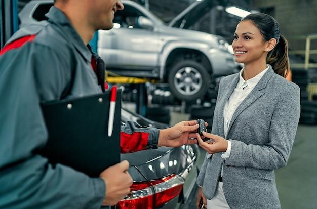 Piękna bizneswoman i mechanik samochodowy dyskutują o pracy i wręczają klucze. naprawa i konserwacja samochodów.
