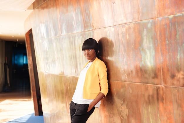 Piękna bizneswoman opierając się o ścianę w biurze