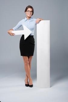 Piękna bizneswoman pokazuje na tablicy