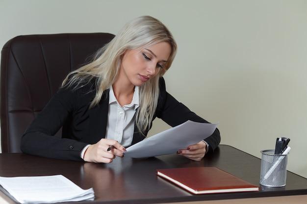 Piękna bizneswoman pracująca przy biurku z dokumentami