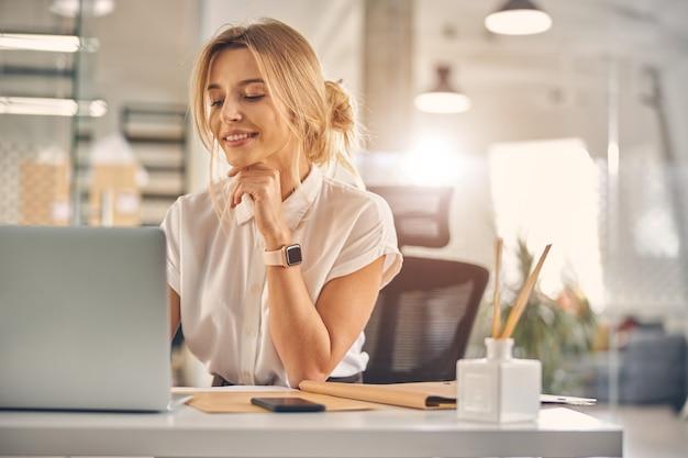 Piękna bizneswoman siedzi przy biurku i uśmiecha się podczas pracy na laptopie
