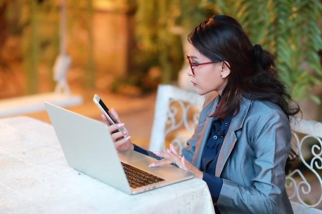 Piękna bizneswoman w okularach sprawdzanie telefonu komórkowego podczas pracy na komputerze