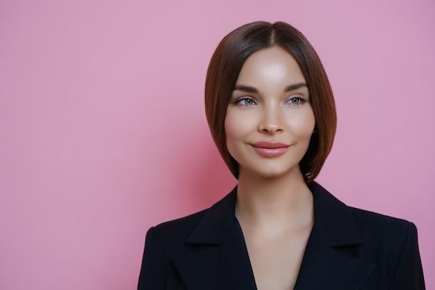 Piękna bizneswoman wygląda na bok z rozmarzonym wyrazem twarzy