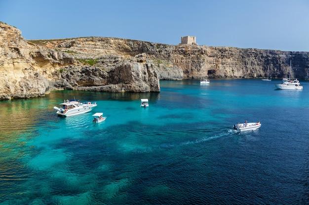 Piękna błękitna laguna z turkusową czystą wodą, jachtami i łodziami w słoneczny letni dzień. comino, malta