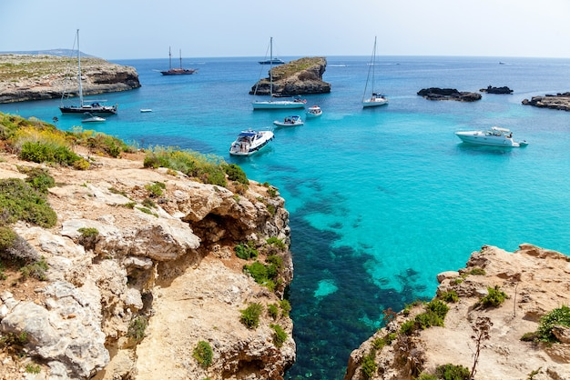 Piękna błękitna laguna z turkusową czystą wodą, jachtami i łodziami w słoneczny letni dzień. comino