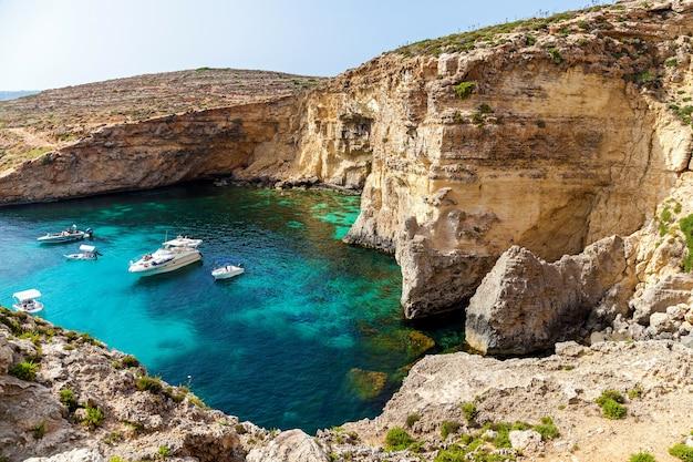 Piękna błękitna laguna z turkusową czystą wodą jachtów i łodzi w słoneczny letni dzień comino