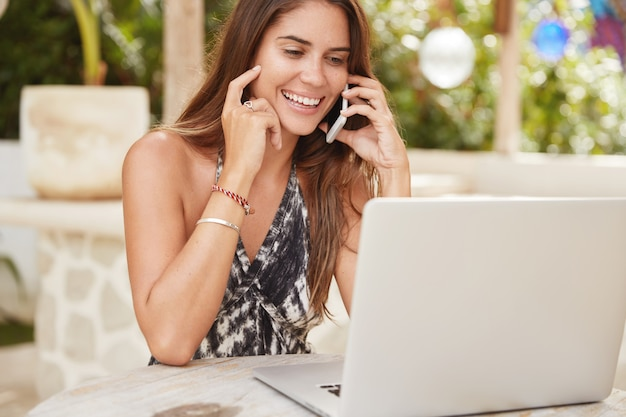 Piękna blogerka przyjemnie rozmawia z przyjaciółką przez telefon komórkowy, lubi komunikację, korzysta z aplikacji na smartfonie, pracuje na laptopie, sprawdza dane, spędza wolny czas w kawiarni