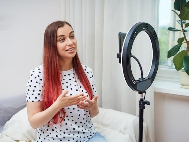 Piękna blogerka w białej koszulce w kropki transmituje online w domu za pomocą lampy pierścieniowej. kobieta komunikuje się z subskrybentami, gestykuluje rękami.