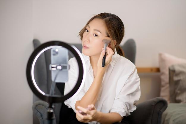 Piękna blogerka zajmująca się makijażem transmituje na żywo, jak używać makijażu twarzy w swoim domu