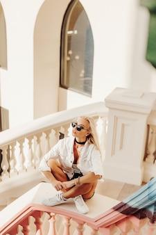 Piękna blond dama zwiedzająca dubrownik po emiratach. fotografia wycieczek po mieście w zatoce. miejski styl życia narodu arabskiego.