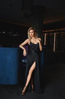 Piękna blond długonoga kobieta o idealnym ciele w czarnej wieczorowej sukni pozuje we wnętrzu luksusowej restauracji