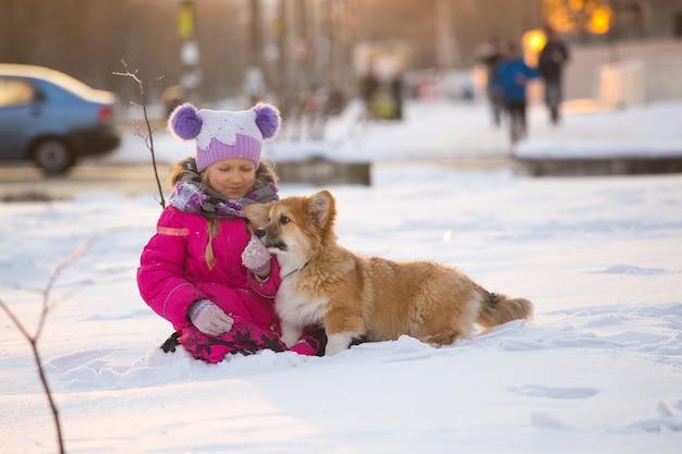 Piękna blond dziewczyna i puszysty szczeniak corgi w zimowy dzień