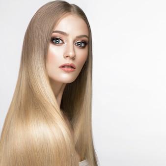 Piękna blond dziewczyna o idealnie gładkich włosach i klasycznym makijażu. piękna twarz.