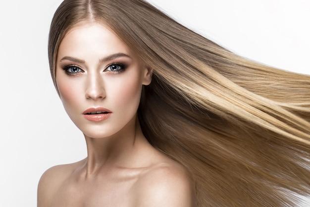 Piękna blond dziewczyna o idealnie gładkich włosach i klasycznym makijażu.