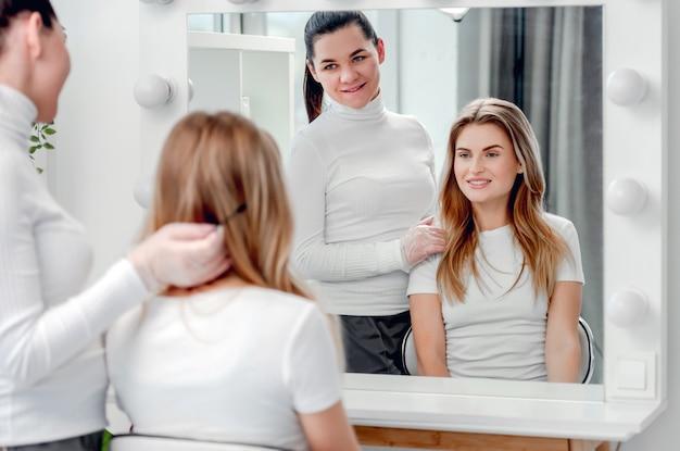 Piękna blond dziewczyna patrząc w lustro na jej microblading brwi i usta makijaż permanentny i uśmiechając się z mistrzem salonu