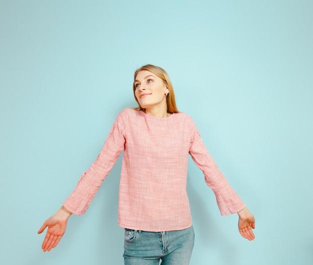 Piękna blond dziewczyna pokazuje gesty na błękitnym tle.