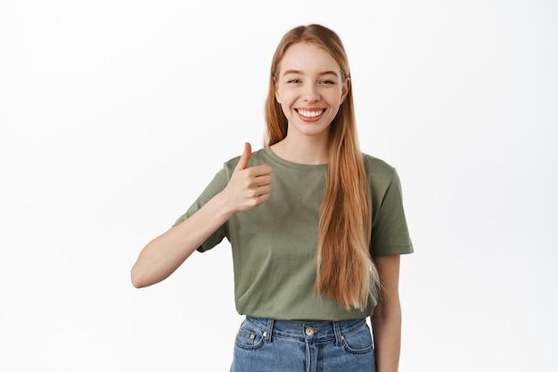 Piękna blond dziewczyna uśmiecha się, pokazuje kciuki z aprobatą, lubi i zgadza się, chwali dobrą robotę, doskonały produkt, poleca firmę, stoi przy białej ścianie