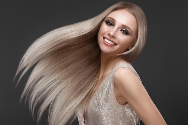 Piękna blond dziewczyna w ruchu o idealnie gładkich włosach i klasycznym makijażu