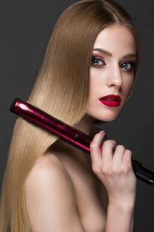 Piękna blond dziewczyna z idealnie gładkimi włosami, curlingiem, klasycznym makijażem i czerwonymi ustami. piękna twarz