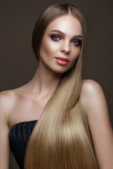 Piękna blond dziewczyna z idealnie gładkimi włosami, klasyczny makijaż. piękna twarz