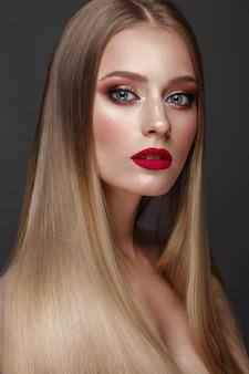 Piękna blond dziewczyna z idealnie gładkimi włosami, klasycznym makijażem i czerwonymi ustami. piękna twarz