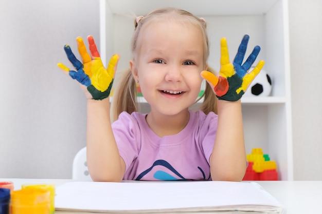 Piękna blond dziewczynka z kolorowym malowaniem na dłoniach, uśmiechnięta radośnie