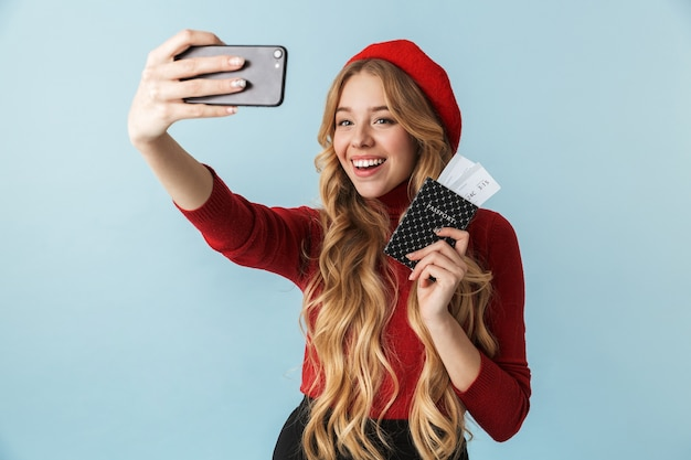 Piękna blond kobieta 20s trzyma paszport i bilet podróżny podczas robienia zdjęcia selfie na telefon komórkowy na białym tle