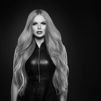 Piękna blond kobieta fryzura długie gładkie kręcone włosy moda makijaż. strzał studio. monochromia. czarny i biały. szary.