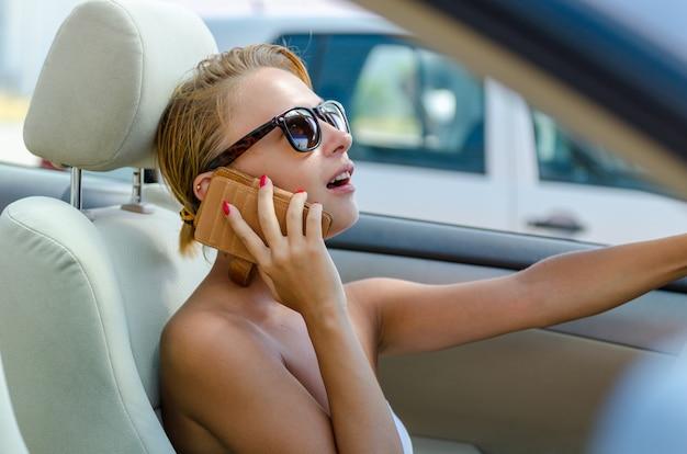 Piękna blond kobieta jedzie swoim kabrioletem